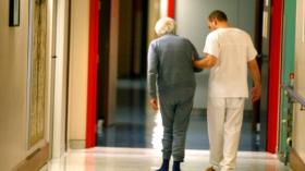 Personne âgée accompagnée d'un soignant dans un couloir d'hôpital