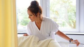 Infirmière près d'un lit dans une chambre